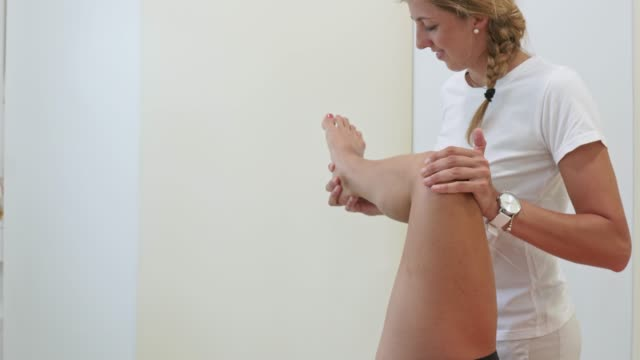 oung woman visiting a physiotherapist after a sports injury - terapia alternativa video stock e b–roll