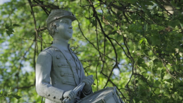 vídeos de stock e filmes b-roll de td 'our drummer boy' clarence d mackenzie statue atop grave monument in soldier's lot with tree branches and leaves hanging overhead - belveder