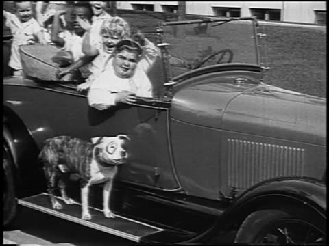 our gang cast sitting in car + waving to camera / dog on running board / newsreel - 1928 stock-videos und b-roll-filmmaterial