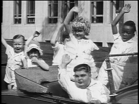 vídeos y material grabado en eventos de stock de our gang cast sitting in car + waving to camera / newsreel - 1928