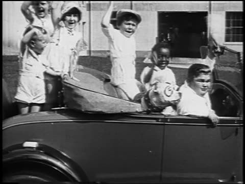 our gang cast sitting in car waving to camera / newsreel - 1928 stock videos & royalty-free footage