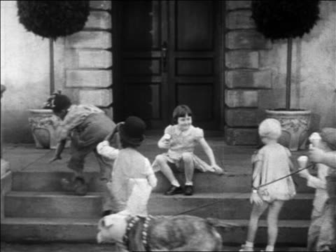 b/w 1931 our gang children sitting on steps of building with ice cream cones / feature - 1931 stock videos & royalty-free footage
