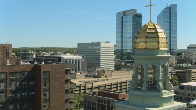 vidéos et rushes de église notre-dame de mount carmel devant downtown white plains, comté de westchester, new york. vidéo aérienne avec le complexe cinématographique ascendant, vers l'arrière et le mouvement de la caméra panoramique. - sunny