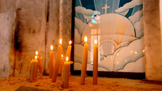 our lady of zeitoun church. candles lit before an icon of the virgin mary who is said to have miraculously appeared above the church in 1968. - 奇跡点の映像素材/bロール