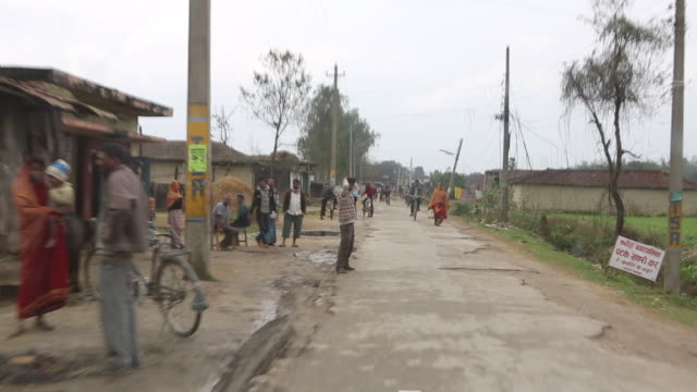 vídeos de stock, filmes e b-roll de ws out of a moving car that is driving on a muddy dirt road while several people on bicycles are passing by in a poor neighbourhood near birgunj a... - fardo