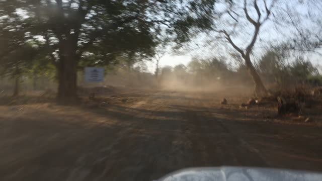 WS out of a moving car that is driving on dirt road in the village Satia a small settlement 300 Kilometer from Kolkata India A big truck can be seen...