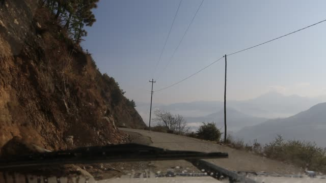 WS out of a windshield of a moving car that is driving around a corner on a narrow road in the mountains near Kathmandu while another vehicle is...