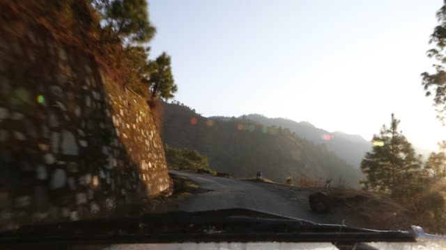 WS out of a windshield of a moving car that is driving on a narrow mountain drive road at sunset near Kathmandu Nepal