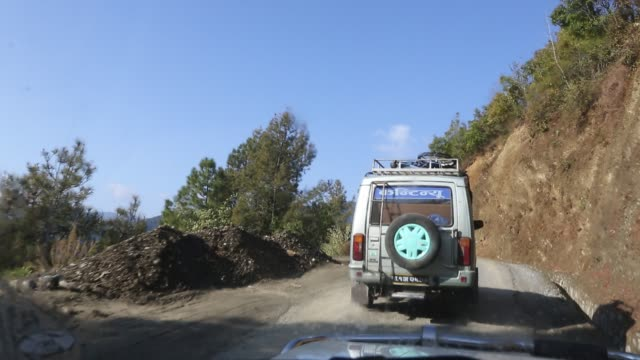 WS out of a windshield of a moving car that is driving on a narrow road in the mountains near Kathmandu Nepal and is following an offroad vehicle