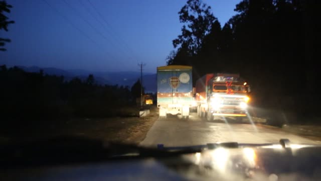 WS out of a windshield of a moving car that is driving on a narrow rural road at night near Kathmandu Nepal Several trucks are can be seen as they...