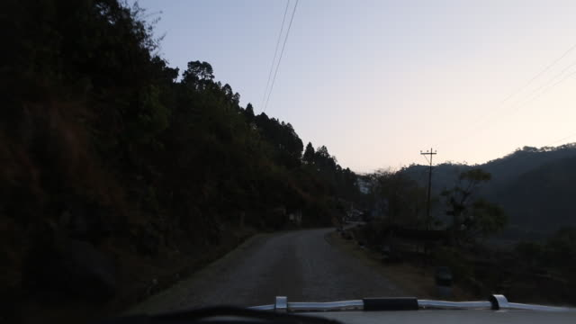 WS out of a windshield of a moving car that is driving on a road in the mountains at dusk near Kathmandu Nepal Several small huts can be seen on the...