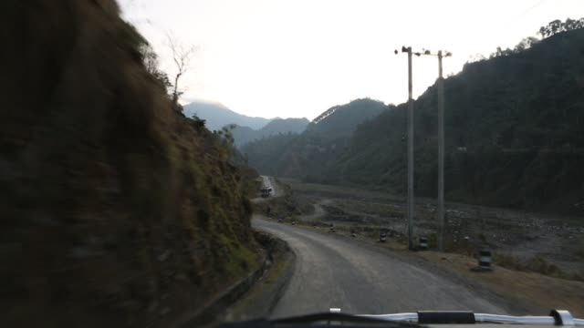 WS out of a windshield of a moving car that is driving on a road in the mountains near Kathmandu Nepal Another vehicle can be seen that is driving in...