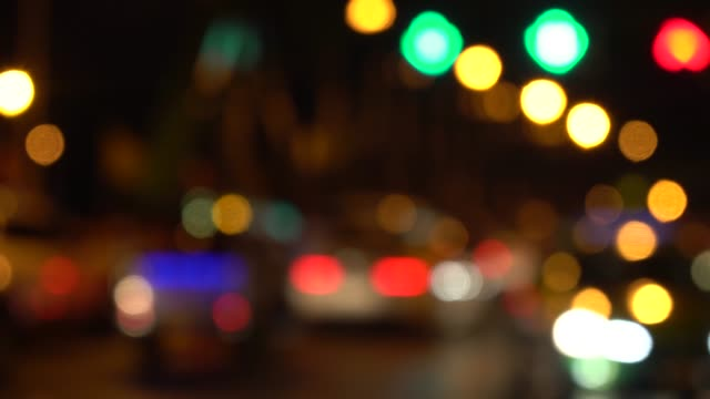 out of focus background with blurry unfocused city lights and driving cars and car light. - anamorphic stock videos & royalty-free footage
