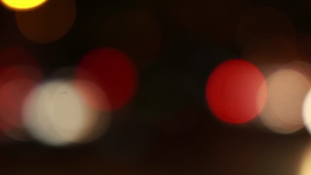 vidéos et rushes de hors de l'arrière-plan de mise au point avec les lumières floues de ville et les voitures de conduite et la lumière de voiture. - anamorphose