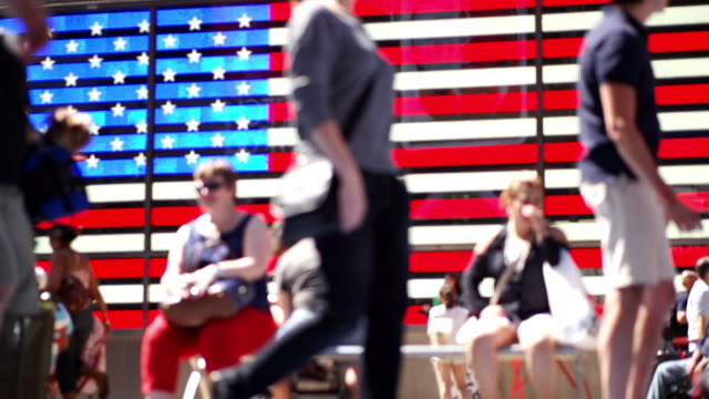 out of focus pedestrians passing large american flag - block shape stock videos & royalty-free footage