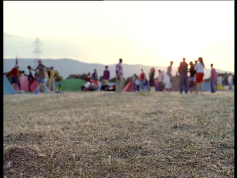 Out of focus people dance and talk by tents in field at music festival