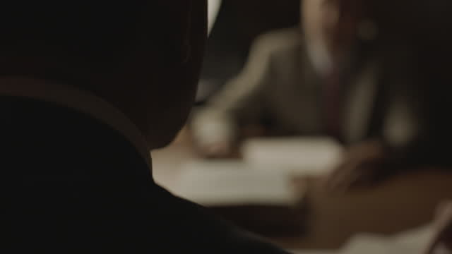 out of focus reenactment shot of a group of men sitting around a table and discussing documents during the 1980s - news event stock videos & royalty-free footage