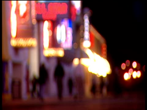 vídeos de stock, filmes e b-roll de out of focus shot down brightly lit street of atlantic city pedestrians walk and lights glitter - atlantic city