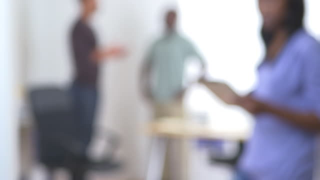 Out of focus shot of business team working in the office