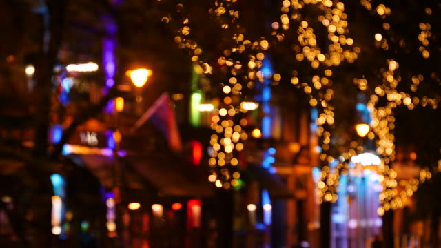 out of focus shot of lights suspended on trees on canal street in manchester at night - rainbow flag stock videos and b-roll footage