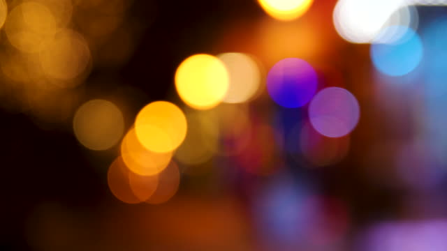 vidéos et rushes de out of focus shot of multi-coloured lights at night - scintillant