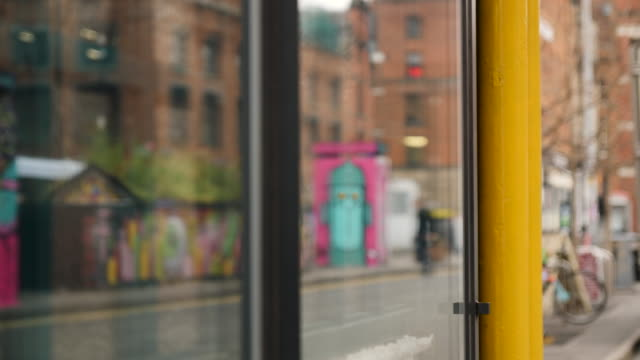 vidéos et rushes de out of focus shot of street art reflected in the window of a bar in the northern quarter, manchester - une seule femme d'âge moyen