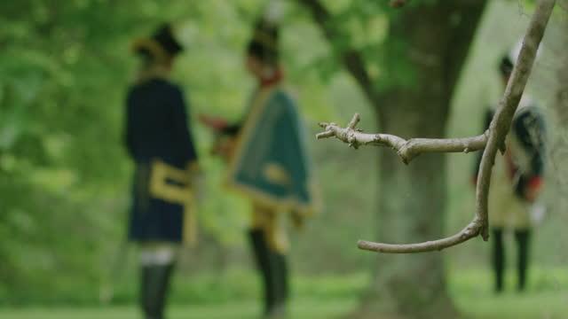 vidéos et rushes de out of focus shot of two men in military uniform talking in the forest - image du xviiième siècle