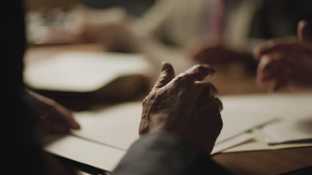 vídeos y material grabado en eventos de stock de out of focus shot reenactment of a group of men sitting around a table and checking documents during the 1980s - espía
