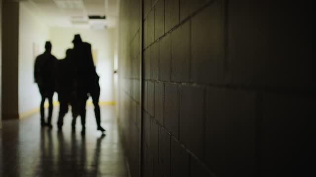 out of focus shot reenactment of two guards leading a prisoner along the corridor and one of them shooting him during the 1980s - watching stock videos & royalty-free footage