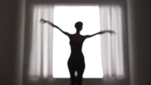 vídeos de stock e filmes b-roll de out of focus woman dancing in front of window - body de ginástica