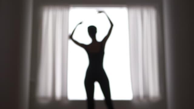 stockvideo's en b-roll-footage met out of focus woman dancing in front of window - gympak