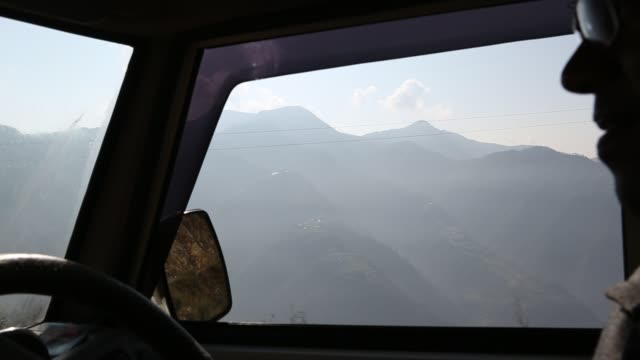 CU out of the side window of a driving car while it is passing the hillside near Kathmandu Nepal The driver of the vehicle can be seen in the...