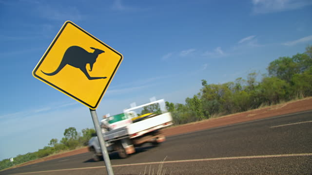 ms outback road sign of 'kangaroo' with car passing / karumba, queensland, australia - animal crossing sign stock videos & royalty-free footage