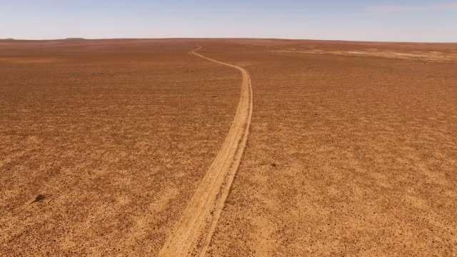 outback track through a stony desert - terreno accidentato video stock e b–roll