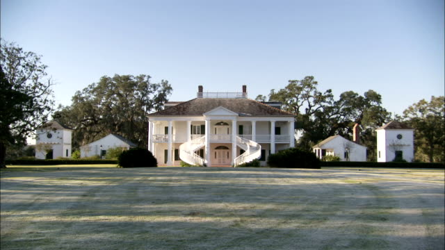 Outbuildings flank a large plantation house. Available in HD.