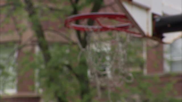 Outdoor basketball hoop w/ partially tattered torn net partial trees building windows BG Street ball bball bball neighborhood recreational park...