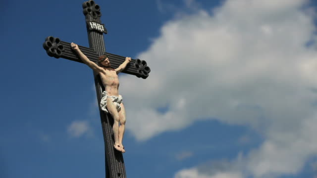 HD Outdoor crucifix against blue sky time lapse