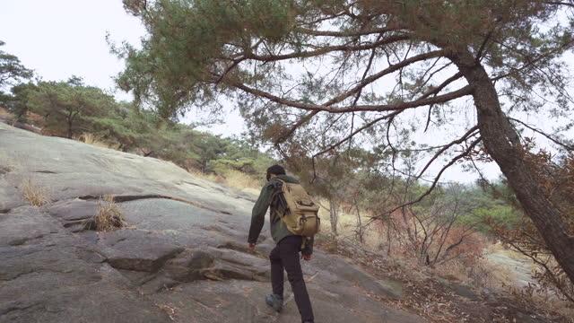 outdoor exercise - young man climbing with backpack - koreanischer abstammung stock-videos und b-roll-filmmaterial