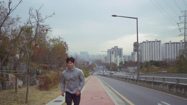 vídeos de stock e filmes b-roll de outdoor exercise - young man running uphill road - membro humano