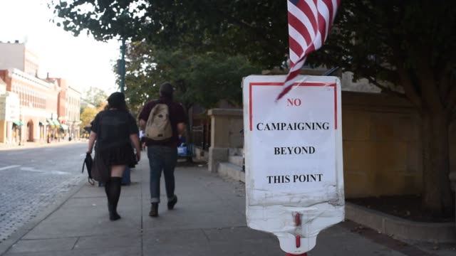 outdoor footage of the early voting process in fairfield and athens county oh on october 29 shots cu of vote here sign on cone with building in... - wahllokal stock-videos und b-roll-filmmaterial