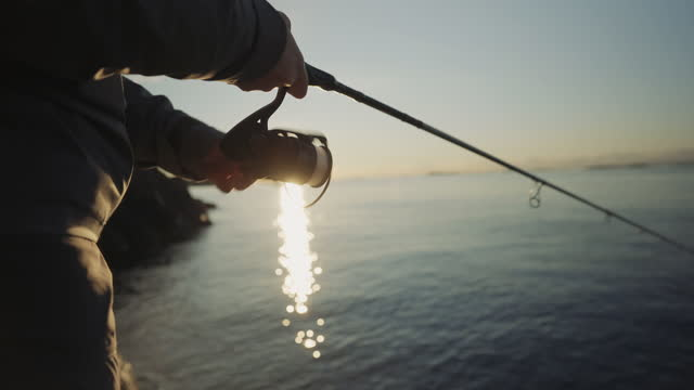 outdoor in norway: woman spinning fishing in the sea with a rod - adventure stock videos & royalty-free footage