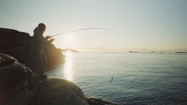 outdoor in norway: woman spinning fishing in the sea with a rod - pollock fish stock videos & royalty-free footage