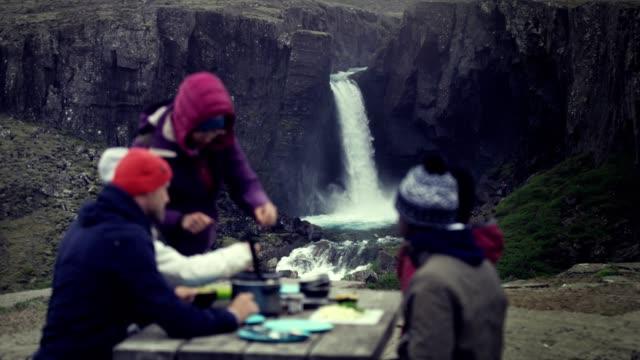 vídeos de stock e filmes b-roll de outdoor meal. group of friends having lunch near waterfall - islândia
