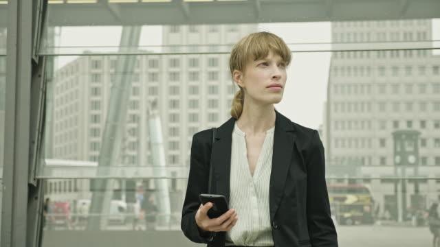 outdoor-mitte erwachsene geschäftsfrau in der berliner innenstadt wartet auf den transport - day stock-videos und b-roll-filmmaterial