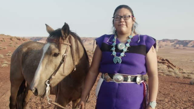outdoor portrait of a beautiful young native american navajo teenage girl in the northern arizona desert near monument valley tribal park at dusk with her horse - indigenous north american culture stock videos & royalty-free footage