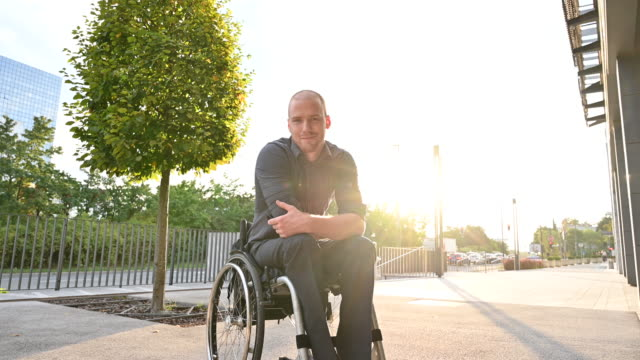 outdoor portrait of smiling young man in wheelchair - full length stock videos & royalty-free footage