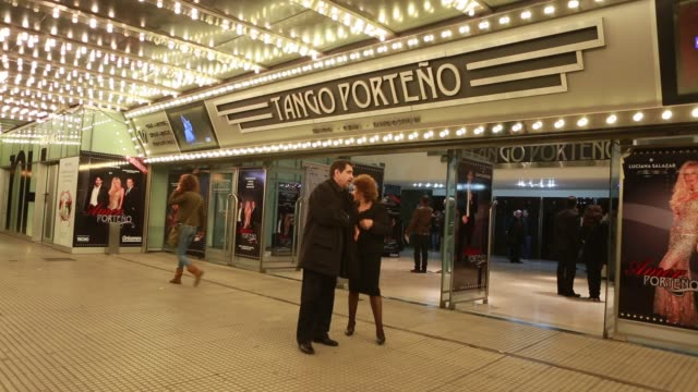 Outdoor shot with advertisement of the tango show Tango Porteno near the Obelisk in Buenos Aires visitors are entering and leaving the building