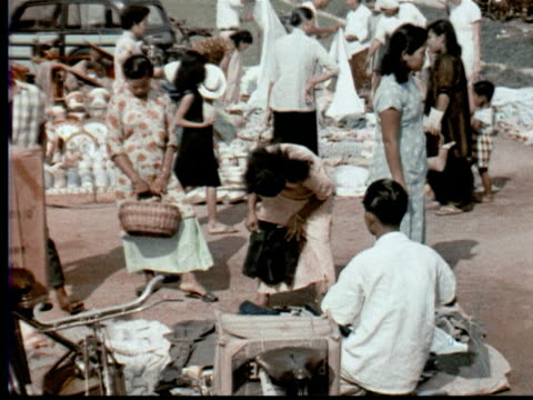 1957 montage outdoor street market. shoppers buying clothing + flowers / singapore / audio - 1957 stock videos & royalty-free footage