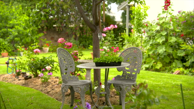 outdoor table and chairs in a beautiful landscaped backyard garden park - front or back yard stock videos & royalty-free footage