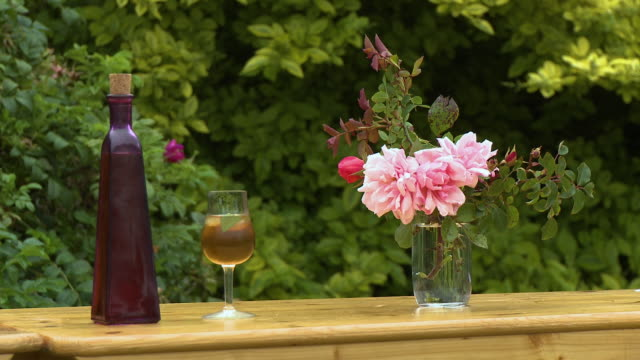 outdoor table with a wineglass and flowers - flower arrangement stock videos & royalty-free footage